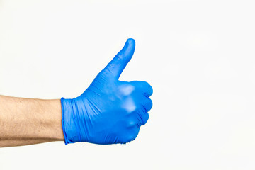 Thumbs up. Profile view of hand in blue medical glove. Outside of hand.