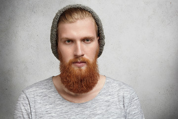 People, style and fashion concept. Isolated portrait of young handsome hipster model with stylish beard and mustache wearing gray warm knitte hat looking at camera with severe or angry expression