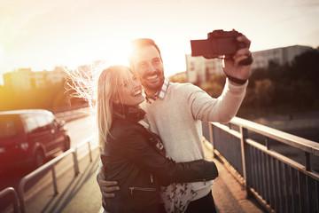 Happy couple taking selfies in city