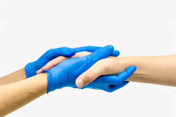 Caring hands with blue medical gloves giving comfort and holding hands.