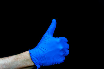 Thumbs up. Hand with blue medical glove on black background.