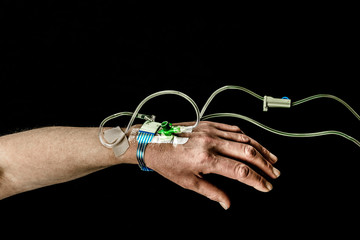 Hand and arm of patient with iv treatment on  black background.