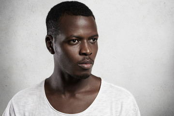 Headshot of handsome young dark-skinned model wearing white t-shirt looking away ahead of him with serious and confident expression on his face, posing indoors. Isolated studio shot, horizontal