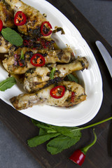 Grilled chicken with lime, chili and herbs. Gray background, white plate, wooden board.