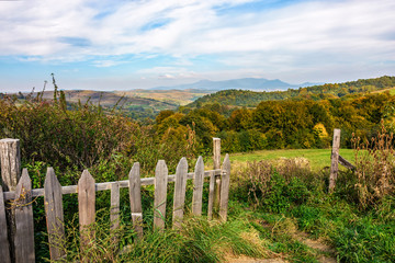 wooden fence on the hillside with forest in agricultural area in mountains early in the morning