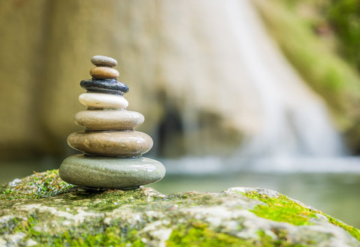 Rock Zen Stack pile of stones in front of waterfall.