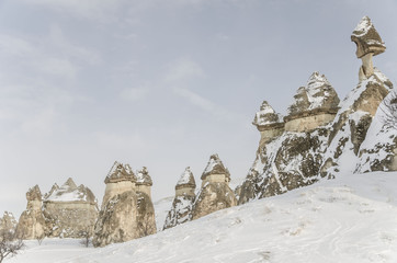 Unique geological rock formations under snow in Cappadocia, Turk