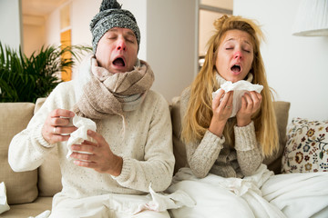 Sick couple catch cold. Man and woman sneezing, coughing, got flu, having runny nose.