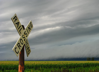 A line of strong thunderstorms approaches a railroad crossing in Illinois farm country.