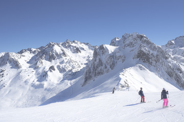Unidentified skiers are on the snowy slope into  Grand Tourmalet ski resort against the mountain range in the French Pyrenees