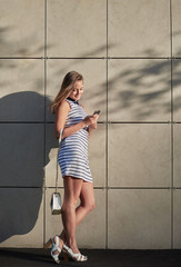 young stylish pretty woman in dress with white and blue stripes stay near wall in the city streets. Girl have a chat or write text by mobile outdoor.