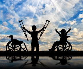 Boy in wheelchair and disabled boy standing with crutches day