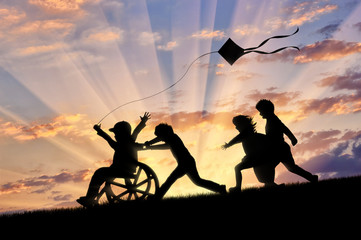 Happy boy in wheelchair playing with children and kite