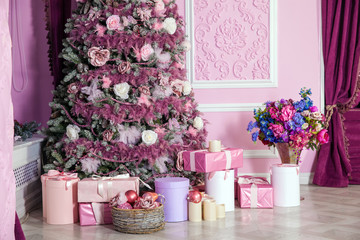 New Year tree decorated in pink toys. Christmas background with presents in room interior
