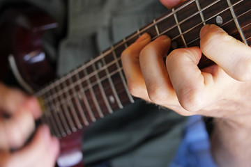 Closeup of a guitarist's hand forming a chord on the fretboard.