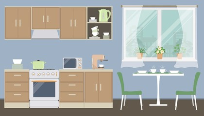 Kitchen in a blue color. There is a kitchen furniture of a beige color, a table, two green chairs, a kettle, a microwave, a coffee machine and other objects in the picture. Vector flat illustration