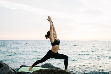 Young woman practicing yoga at rocky seashore at sunrise or sunset