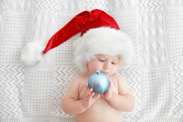 Little baby in Christmas hat with toy on white bed