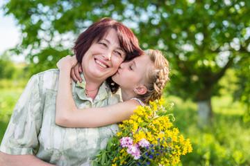 Kisses granddaughter grandmother in the green garden