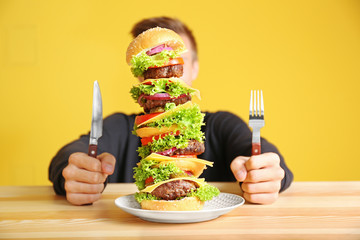 Man eating huge burger at table Wall mural