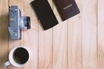 Vintage camera, coffee cup and passport on wooden table, Tourist concept