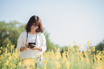 Young woman with camera in the Sunhemp garden