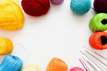 Colorful threads and knitting accessories frame, free space. Bright balls of yarn with needles and crochets on white background, copy space for text. Leisure, handiwork, hobby concept
