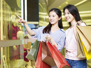 two young asian women shopping in mall