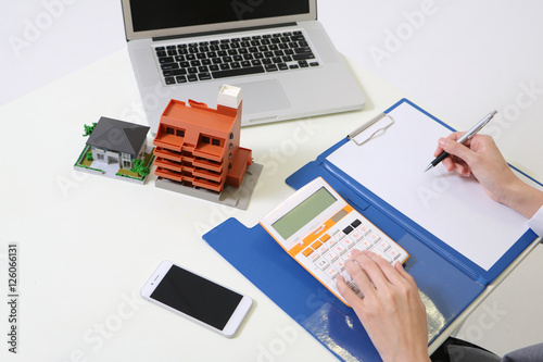 Woman Uses Calculator And House Building Miniature Models