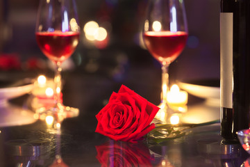 Beautiful rose on a table surrounded by candle lights. Romantic dinner setting..