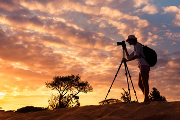 Female photographer taking picture in a beautiful nature setting. Adventure and travel concept.
