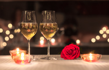 Romantic dinning concept. Pair of wine glasses on a table next to red rose.