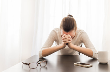 Young woman sitting in her office feeling desperate. Praying and emotion concept.