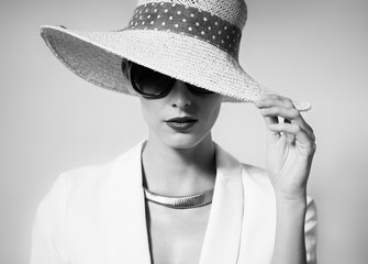 Black and white fashion portrait of female wearing hat.