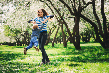 happy mother and toddler son playing outdoor in spring or summer park, family activities on the walk