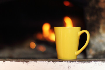 warming atmosphere of home comfort/ yellow ceramic mug is the old fireplace on the background of fire