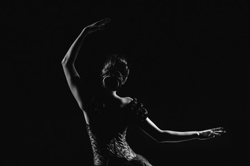 Light silhouette of elegant young ballerina standing back to camera in third position arms petite pose on the black background