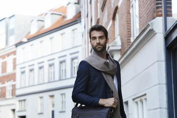 Smart man in scarf in city