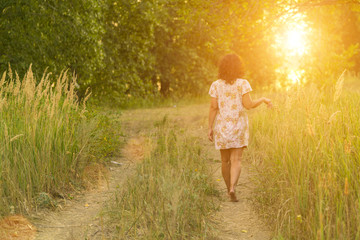 Adult brunette woman in a dress walking on a meadow path in the sunlight, view from the back