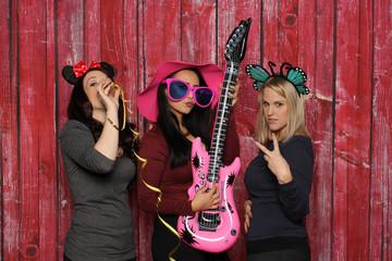 3 Mädchen haben Spaß mit einer Fotobox - Mädchentrio vor rotem Hintergrund mit Photobooth