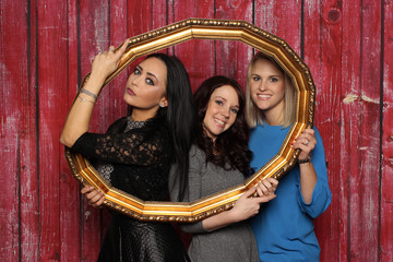 Mädchentrio schaut durch einen Bilderrahmen - 3 hübsche junge Frauen vor einer Fotobox