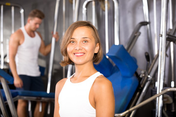 Woman sitting on bench between exercises in gym