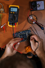 Electrician checking circuit board with multimeter