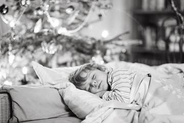 Little cute kid boy sleeping under Christmas tree
