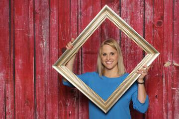 Blondes Mädchen schaut durch einen Bilderrahmen - Junge Frau hält einen großen Bilderrahmen