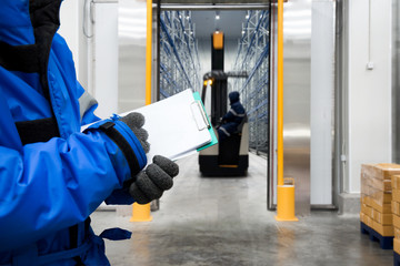 Hand of worker with clipboard checking goods in freezing room or warehouse