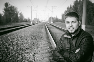 young man sitting on tracks. bearded guy in jacket and jeans, sitting on rails and sleepers on rail until train arrived. against background of the autumn landscape and gravel, expects the new travel