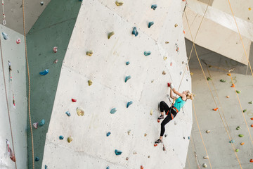 Sporty young woman exercising in a colorful climbing gym