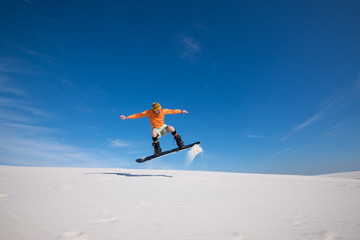 Snowboarder is flying over the sand dune.
