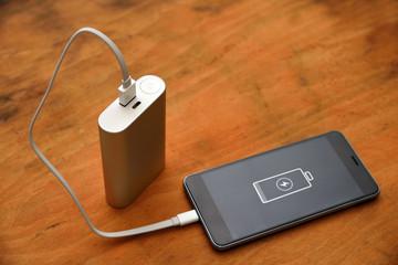 Smartphone with powerbank on wood